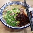 Signature beef noodles with chili.
