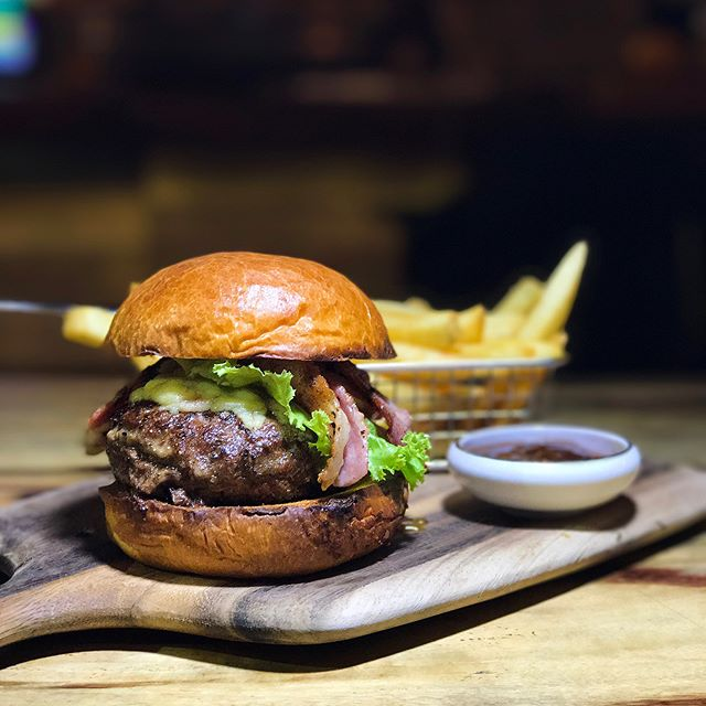 Royal Armoury Burger —$19 Charcoal grilled wagyu beef slathered with onion jam and layered with maple glazed bacon.