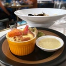 Lobster soufflé accompanied by a tasty lobster bisque with lots of ingredients!
