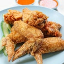 """They are not kidding with the stall name by having the word """"famous"""" in it, because it is truly popular when you see long queues just for their fried chicken wing ($1.20), and people are buying by the packets or plates."""