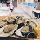 Would u like some big fresh oysters, peeled and served right up to u, at the heart of a seafood market.