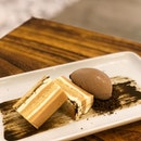 [Kinako Hojicha-$9.80]  A limited-time only special, this artfully plated dessert features layers of buttercream, kinako-flavoured sponge and kinako ganache.