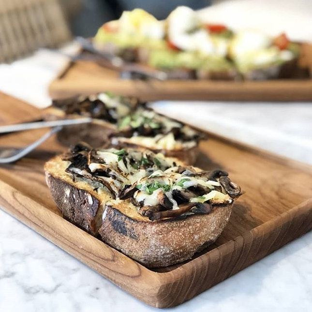 Open-face toast with roasted mushroom, creme fraiche and melted cheese.