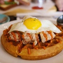 Sundried Tomato & Herb Waffles with fried chicken, tangy pineapple salsa, 'bulldog' mayo and sunny side egg