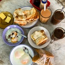 Of buttered toast, soft boiled eggs, potato epok epok, coffee and tea.