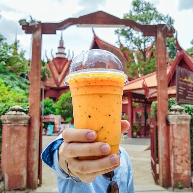 Beating the heat with a cup of Mango Passion Fruit Shake while exploring the bustling neighborhood of Phnom Penh.