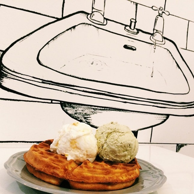 Mango cheesecake and pistachio ice cream on a waffle.