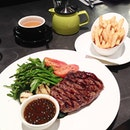 Scotch steak [$32] served with grilled veggies and fries.