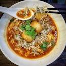 A bowl of meesua in chilli crab gravy.