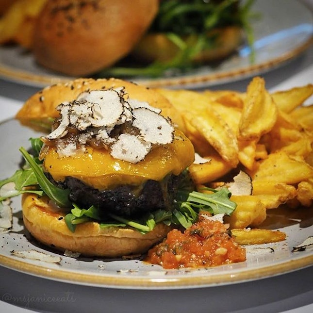 ⭐ District 10 Bar & Grill ~ Black Truffle Wagyu Burger ⭐  Get ready to chomp on District 10's tantalising Black Truffle Wagyu Burger which consists of a thick and deliciously juicy wagyu beef patty, sweet caramelised onions, melty cheddar cheese and fresh wild rocket, served with appetising tomato salsa and crispy D10 fries.