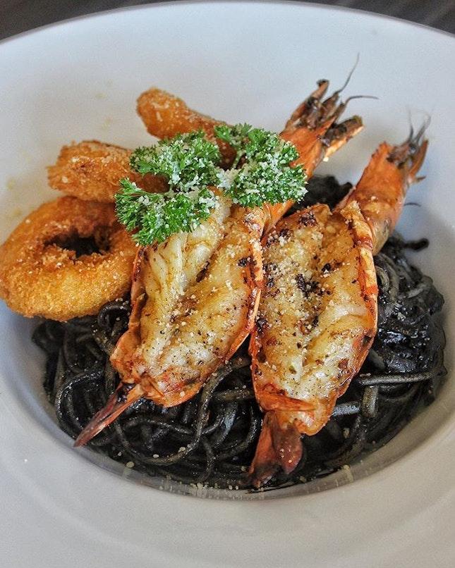 Spaghetti al nero di Seppai-Squid Ink Pasta with Tiger Prawns and Crispy Calamari Rings ($20.90++) Comb through al denta strands of squid ink spaghetti, tossed generously in squid ink sauce.