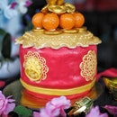 1.3kg Drum of Fortune ($108 nett) Chocolate marble cake coated with fondant, and topped with eight lucky Mandarin oranges made with dark chocolate and mini chocolate ingots.