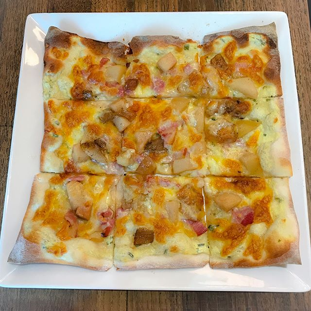 Alsatian tarte flambé [$16++] A 20-30 min waiting time is required for this baked flatbread topped with sour cream, sliced onions, bacon bits, thyme, caramelised apples and mozzarella cheese.