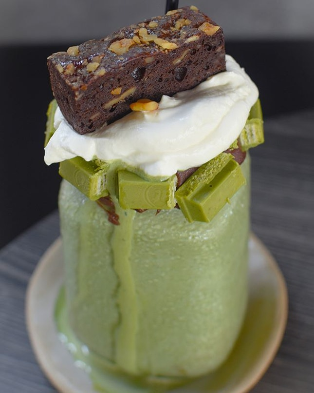 Matcha maniac [$10++] Matcha thickshake served in a mason jar topped with Chantilly cream, a slice of walnut brownie and smeared with Nutella and green tea KitKat on its rim.