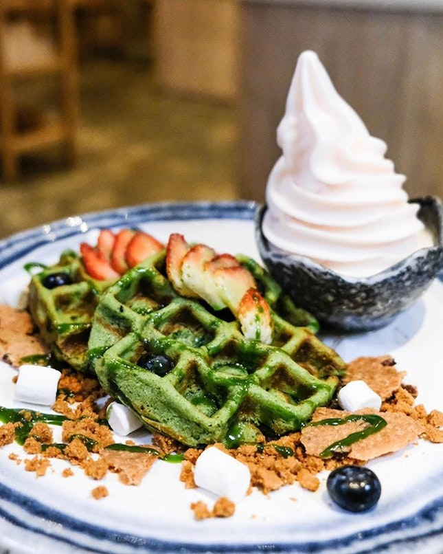 Homemade mochi waffles with cacao nib sable, cookie crumble and fresh fruits drizzled in matcha sauce.