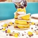 Nicely stacked mini pancakes with mango and whipped cream.