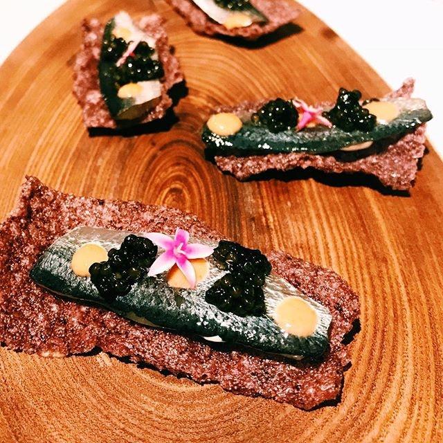 Sardines on purple rice crackers as snacks.