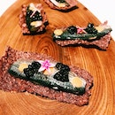 Sardines on purple rice crackers as snacks.