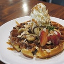 Freshly baked caramel banana waffle with honeycomb toffee ice cream, toasted almonds, strawberries and chocolate sauce.